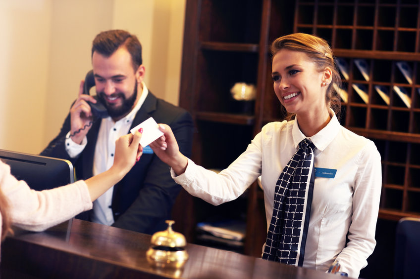 a man and a woman working at the front desk of a hotel